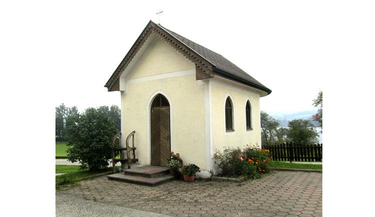 Blick auf die Kapelle, seitlich Blumen, im Hintergrund ein Zaun