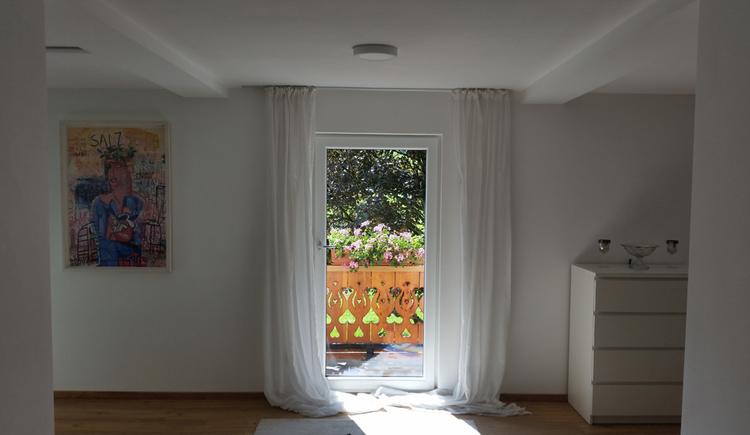 Blick auf den Balkon, seitlich eine Kommode