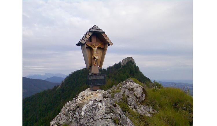 Blick auf ein Holzmarterl am Gipfel