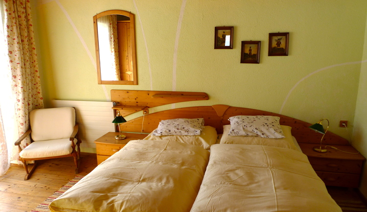 The bedroom is equipped with lots of wood and a double bed.