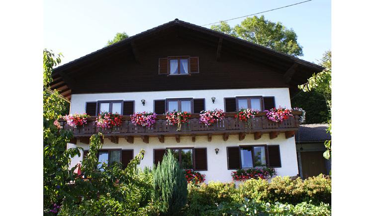 Blick auf das Haus mit Balkon und Blumen, im Vordergrund Sträucher