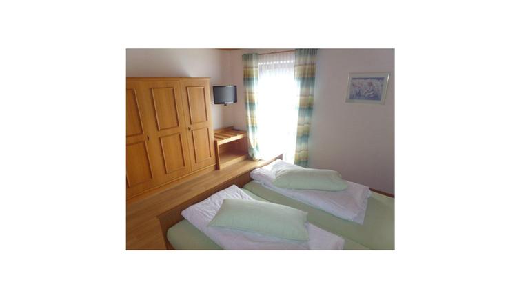 Schlafzimmer mit Doppelbett, im Hintergrund Kleiderschrank, Fernseher auf der Wand montiert, Balkontür