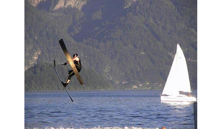 Wasserskifahrer, Segelboot, See, im Hintergrund Wälder. (© Tourismusverband MondSeeLand)