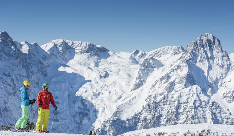 2 Skifahrer im Skigebiet Hinterstoder, im Hintergrund die schnee-bedeckten Berge. (© Pyhrn-Priel)