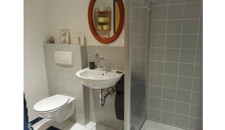 Blick in das Badezimmer mit Toilette, Waschbecken, Spiegel