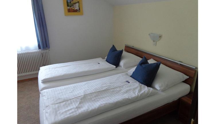 Schlafzimmer mit Doppelbett, im Hintergrund ein Fenster, darunter Heizkörper