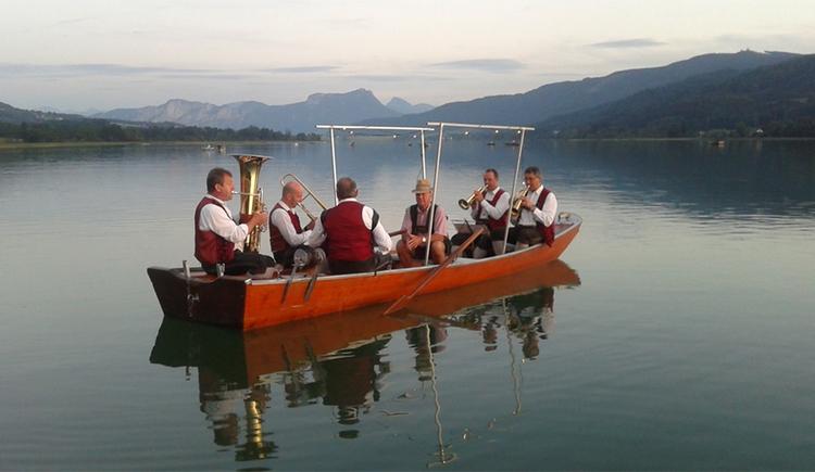 Musikanten sitzen im Boot auf dem See. (© Tourismusverband MondSeeLand)