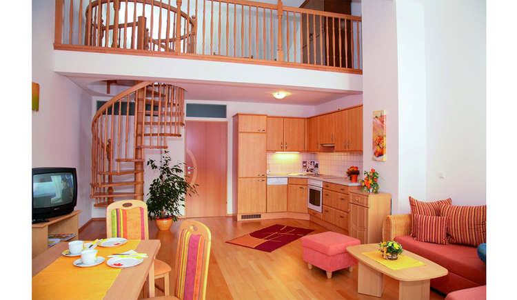 Living area with dining table and chairs in the foreground, TV, couch, stool and small table, in the background the kitchen with dishwasher, sink, stove, spiral staircase in the background