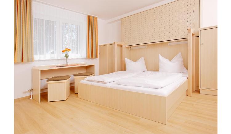 Schlafzimmer mit Doppelbett, Schränke, seitlich ein länglicher Tisch mit Hocker, Fenster