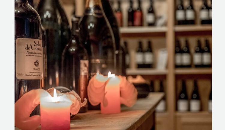 im Vordergrund Kerzen und Flaschen, im Hintergrund Regale mit Flaschen