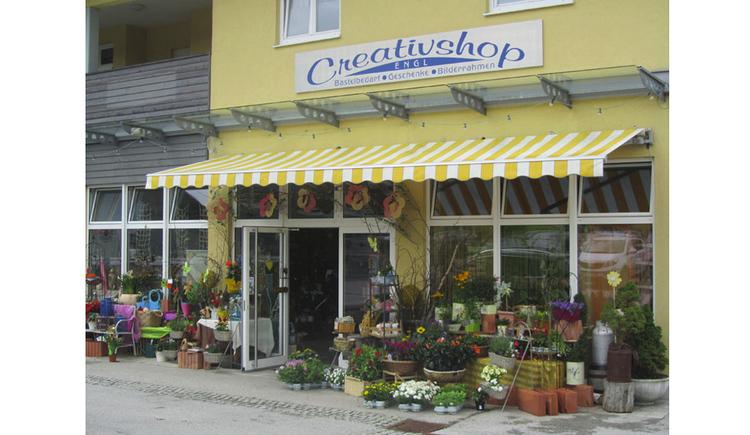 Blick auf das Geschäft, im Vordergrund Blumen, Töpfe