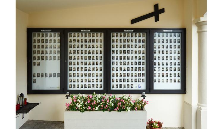 Blick auf die Gedenktafel, im Vordergrund Blumen
