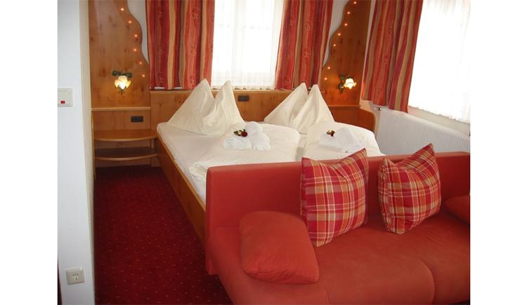 Schlafzimmer mit Doppelbett , im Vordergrund Couch mit Polster