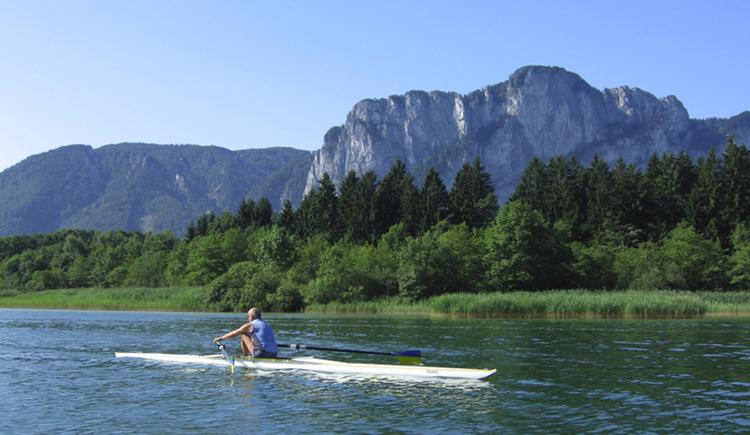 Ruderboot am See, im Hintergrund die Landschaft, Bäume, Berge