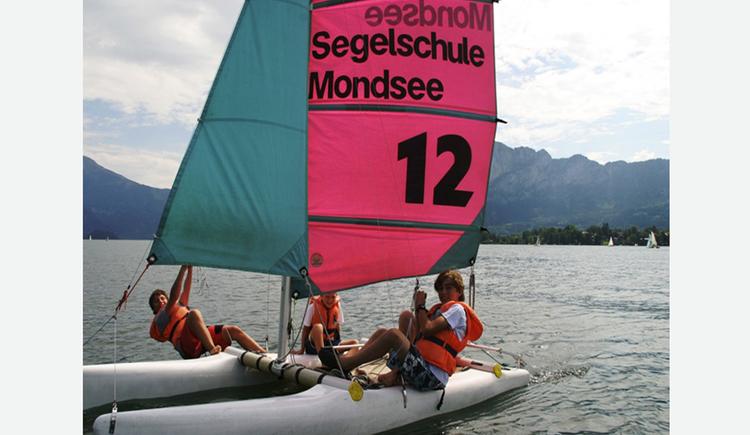 Three persons on a sailing boat at lake Mondsee. (© Segelschule Mondsee)