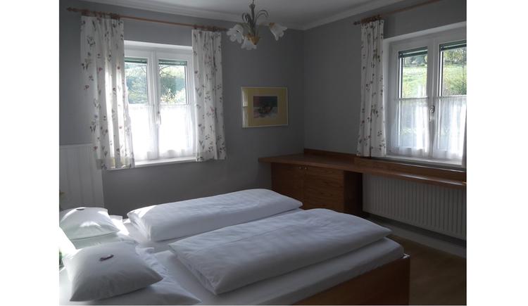Schlafzimmer mit Doppelbett, seitlich Ablagemöglichkeit, im Hintergrund Fenster