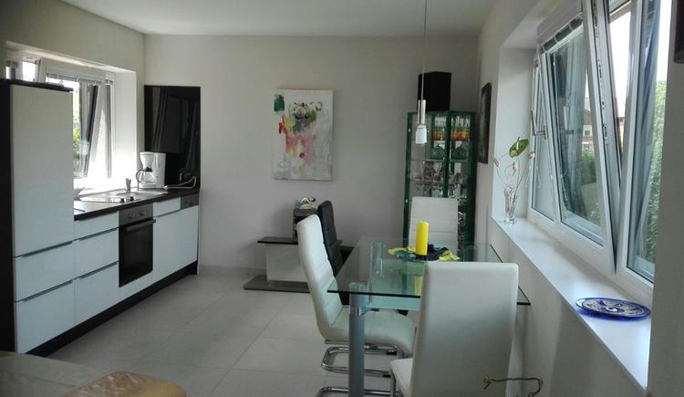 Wohnbereich mit Küche, Tisch und Stühlen