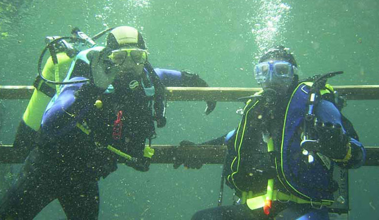 Two divers with complete equipment underwater