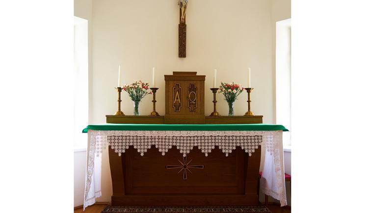 Blick auf den Altar mit Kerzen und Blumen