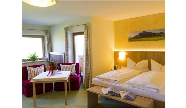 Doppelbett, davor eine kleine Bank, im Hintergrund seitlich Sesseln und ein Tisch, Fenster, Balkontür