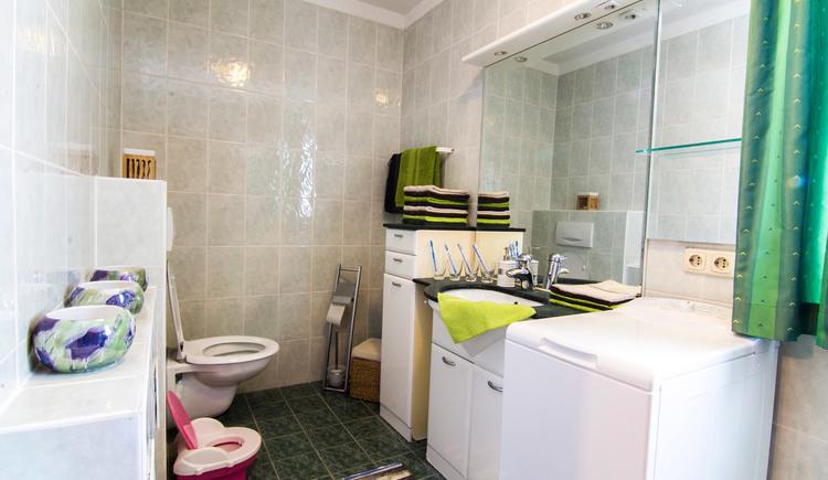 Badezimmer mit Toilette, Waschtisch und Waschmaschine