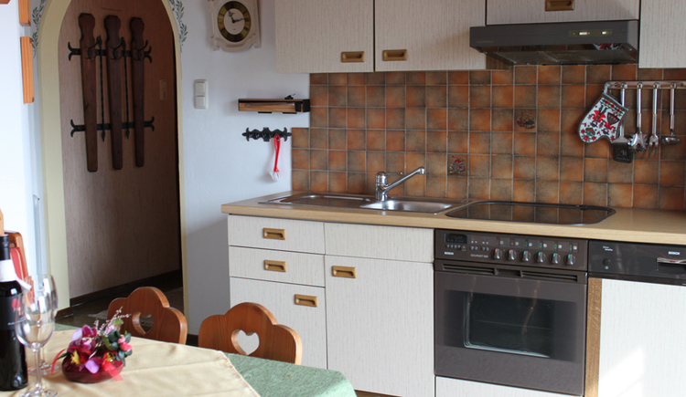 look at the kitchen with cooker and dishwasher, table with chairs in the foreground