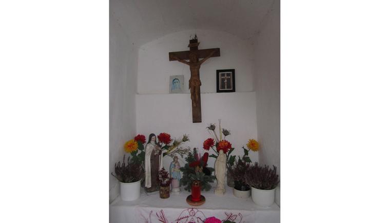 Blick auf den Altar, Blumen, Kreuz, Heiligenfigur, Kerzen