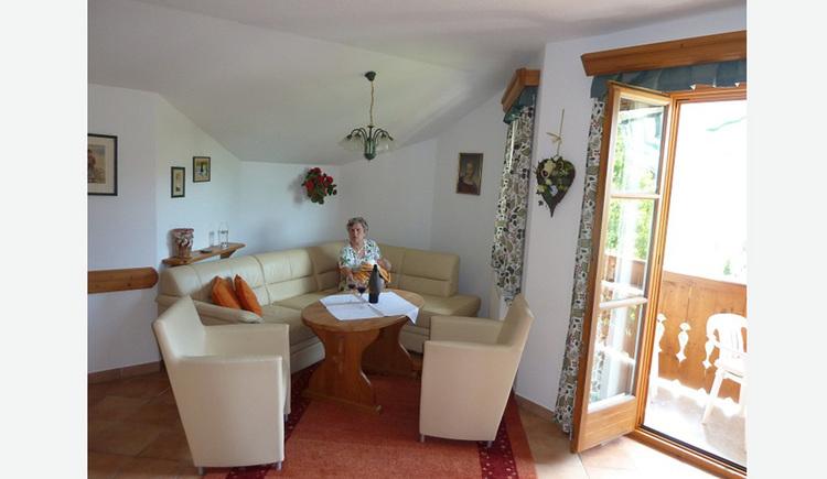 Wohnbereich, Person sitzt auf einer Couch, Tisch, Sesseln, seitlich Blick durch die offene Balkontür auf den Balkon