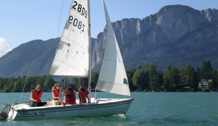 A sailing boat with some persons on the boat, in the background there are mountains.