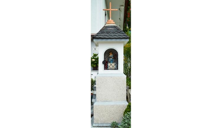 Blick auf den Bildstock, hinter Gitter eine Heiligenfigur