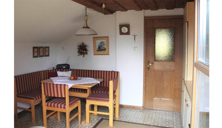Essbereich mit Eckbank, Tisch, im Hintergrund ein Radio, Bilder an der Wand