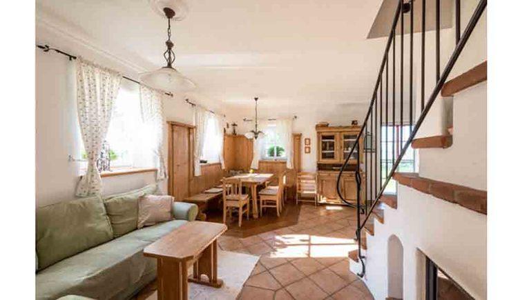 Wohnbereich mit Couch, Tisch, im Hintergrund ein Esstisch mit Stühlen, seitlich die Stiege mit einem Geländer