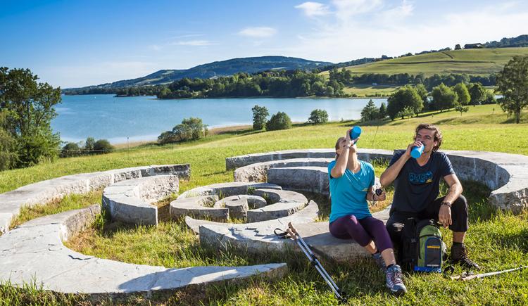 Eine junge Frau und ein junger Mann machen beim Wandern eine Pause und trinken aus ihren Wanderflaschen. Im Hintergrund sind See und Wiese. (© Valentin Weinhaupl, Mondsee)