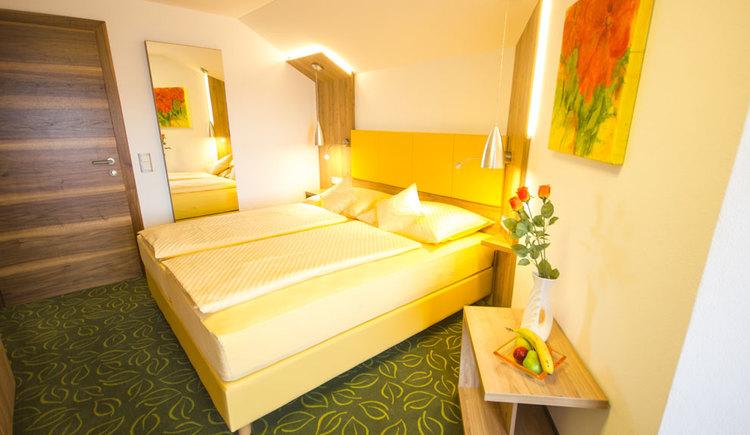 Schlafzimmer mit Doppelbett, im Hintergrund ein Spielgel, vorne steht seitlich ein kleiner Tisch mit einer gefüllten Obstschale, Teppichboden