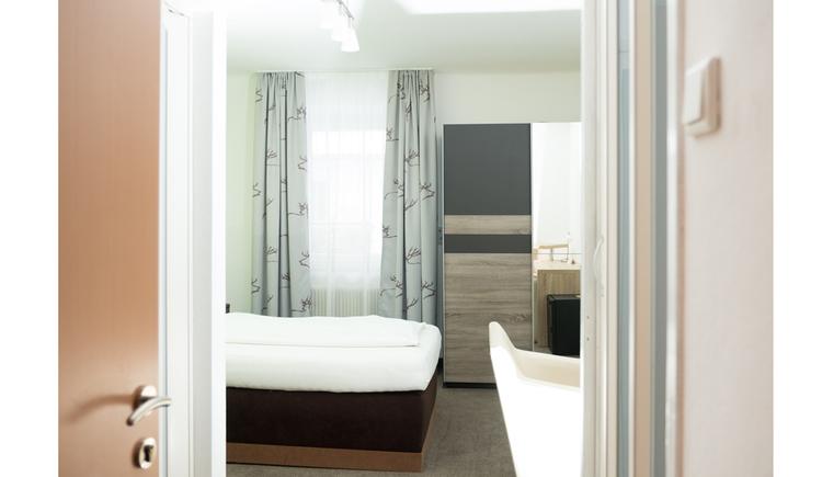 Einzelbett, Stuhl, im Hintergrund Fenster und Kleiderschrank