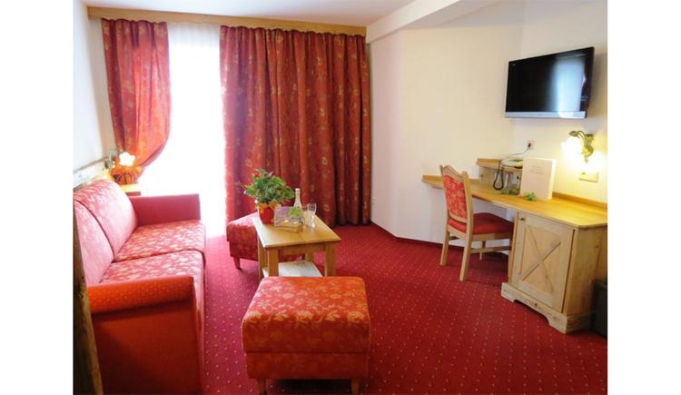 Wohnbereich mit Couch, Tisch, Hocker, im Hintergrund Balkontür, seitlich ein Tisch mit Stuhl, darüber ein Fernseher
