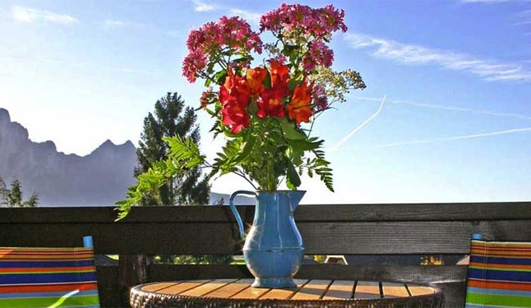 mountains in the backgroun, flower vase in the foreground