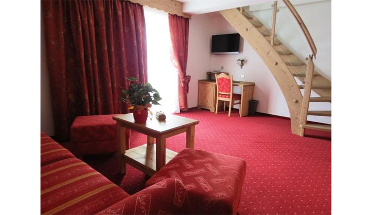 Wohnbereich mit Couch, Tisch und Hocker, Balkontür, Tisch und Stuhl, darüber ein Fernseher, Holzstiege