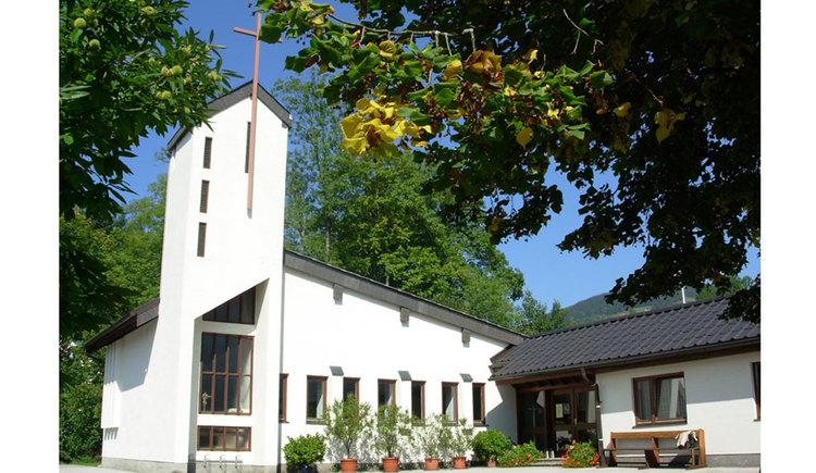 Außenansicht der Evangelischen Pfarrkirche in Mondsee, mit einigen Pflanzen vor der Kirche und Bäumen auf der Seite