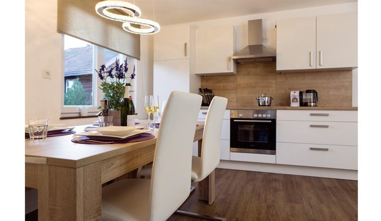 im Vordergrund Tisch und Stühle, im Hintergrund die Küche mit Herd, Kaffeemaschine, Wasserkocher, seitlich ein Fenster
