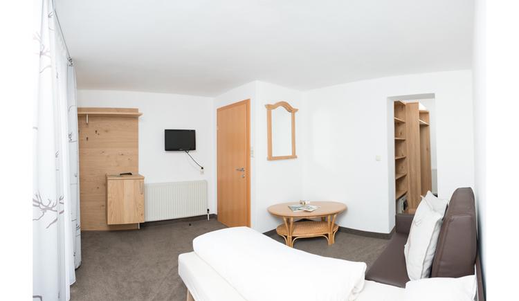 Doppelbett, Tisch, im Hintergrund Fernseher an der Wand