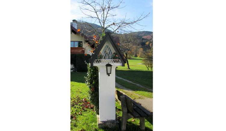 Blick auf den Bildstock, davor eine Holzbank seitlich, im Hintergrund Wiesen, Bäume, Haus