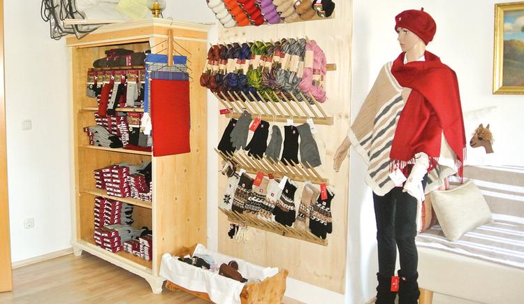 Socken in einem Regal, Handschuhe, Kleiderpuppe mit Haube und Ponchos, Hose