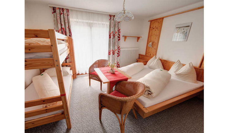 Double bed, in front of it a table with chairs, on the side a bunk bed, in the background a balcony door