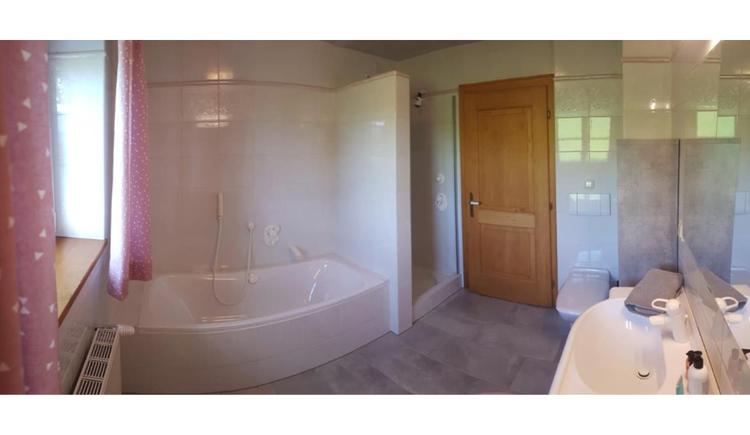 seitlich ein Waschbecken, im Hintergrund eine Badewanne