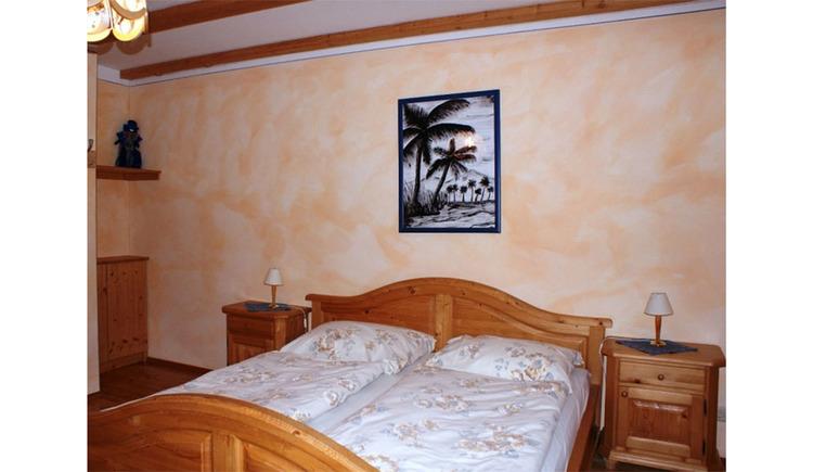 Schlafzimmer mit Doppelbett, Nachtkästchen mit Tischlampen, im Hintergrund ein Bild