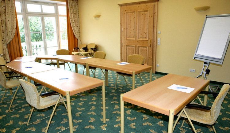 chairs and tables with writing utensils and a flipchart. (© Eichingerbauer)