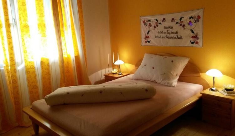Schlafzimmer mit Einzelbett, Nachtkästchen und Lampe