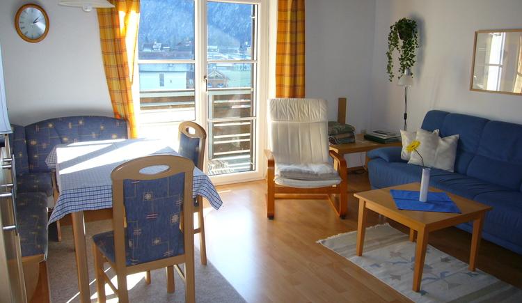 Heller, freundlicher Wohnbereich mit gemütlicher Couch, Essbereich und Zugang zum Balkon