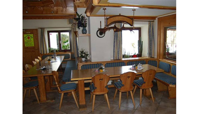 """Inn \""""Gaststube\"""" with corner bench, tables, chairs, background window"""